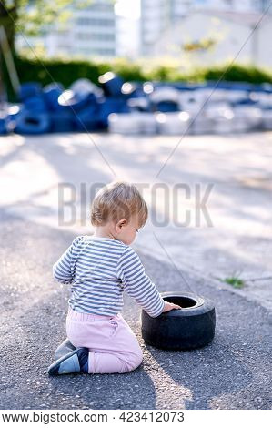 Baby Kneels And Touches The Rim Of The Car In The Parking Lot