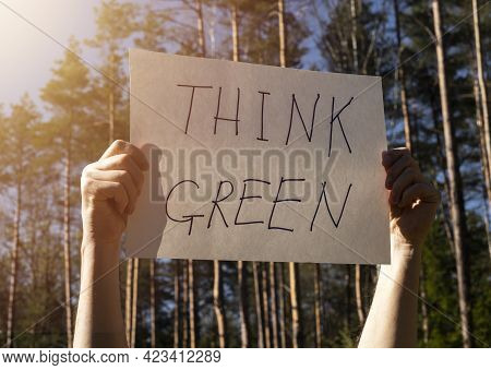 Think Green Written On Paper Card, Poster In Male Hands.