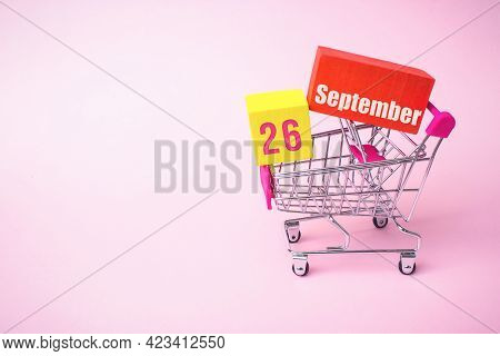 September 26th. Day 26 Of Month, Calendar Date. Close Up Toy Metal Shopping Cart With Red And Yellow
