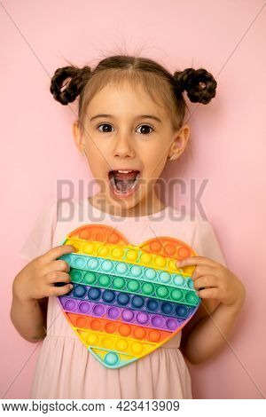 The Girl With Pigtails Bulged Her Eyes In Surprise, Holding A Popit Toy In The Shape Of A Heart In H