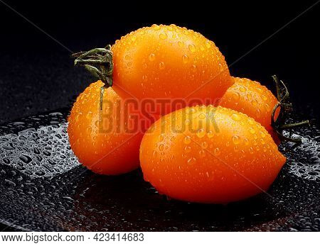 Beautiful Yellow Tomatoes Lie On A Black Plate On A Black Background.