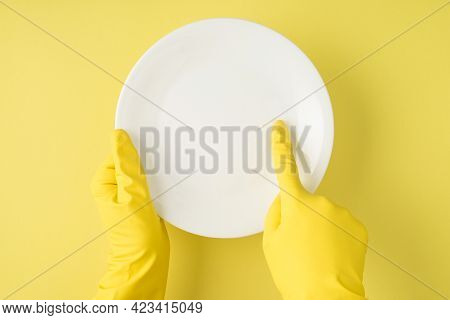 Top View Photo Of Hands In Yellow Rubber Gloves Indicating With Forefinger On Clear White Plate On I
