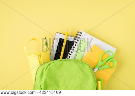 Overhead Photo Of Backpack Ruler Notepad Pen Pencil Tablet And Pencil-box Isolated On The Yellow Bac