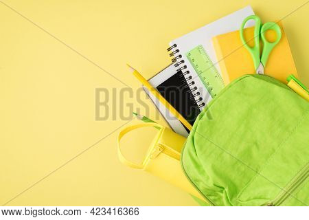 Above Photo Of Backpack Ruler Notepad Pen Pencil Tablet And Pencil-box Isolated On The Yellow Backgr
