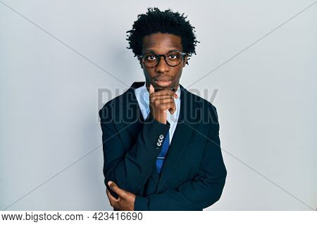 Young african american man wearing business suit and tie relaxed with serious expression on face. simple and natural looking at the camera.