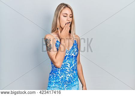 Young beautiful caucasian woman wearing summer dress bored yawning tired covering mouth with hand. restless and sleepiness.