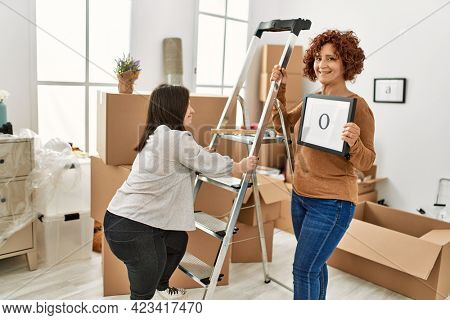 Mature mother and down syndrome daughter moving to a new home, standing by cardboard boxes