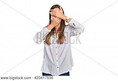 Young beautiful woman wearing casual clothes covering eyes and mouth with hands, surprised and shocked. hiding emotion