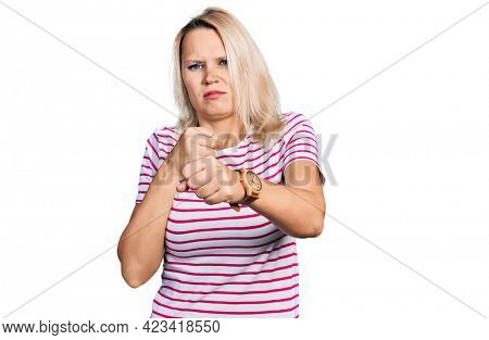 Young caucasian woman wearing casual clothes punching fist to fight, aggressive and angry attack, threat and violence