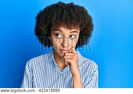 Young hispanic girl wearing casual clothes thinking concentrated about doubt with finger on chin and looking up wondering
