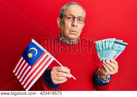 Handsome senior man with grey hair holding malaysia flag and malaysian ringgit banknotes clueless and confused expression. doubt concept.