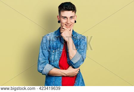 Young caucasian boy with ears dilation wearing casual denim jacket looking confident at the camera smiling with crossed arms and hand raised on chin. thinking positive.