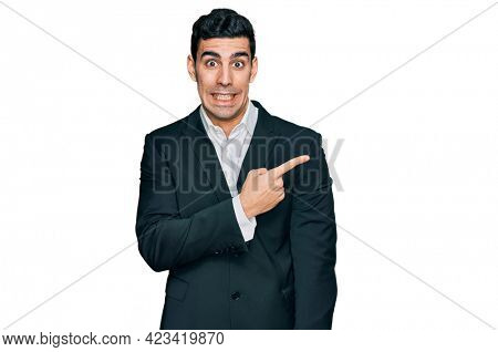 Handsome hispanic man wearing business clothes pointing aside worried and nervous with forefinger, concerned and surprised expression