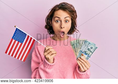 Young brunette woman holding united states flag and dollars afraid and shocked with surprise and amazed expression, fear and excited face.