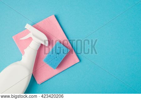 Above Photo Of Pink Cleaning Rag Spray And Blue Cellulose Sponge Isolated On The Blue Background