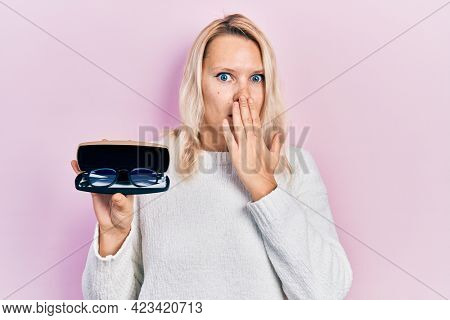 Beautiful caucasian blonde woman holding glasses in eyewear case covering mouth with hand, shocked and afraid for mistake. surprised expression