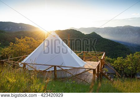Beautiful Panorama Of Glamping House Tent In The Morning Sun Light On Wooden Deck With Fence And Fog
