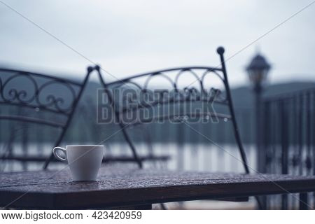Closeup Detail Of White Small Espresso Coffee Cup On Wooden Table With Rain Drops On Rainy Outdoor R