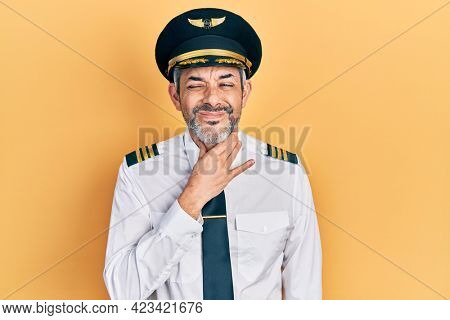 Handsome middle age man with grey hair wearing airplane pilot uniform touching painful neck, sore throat for flu, clod and infection