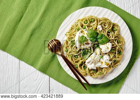 Spaghetti Salad With Pesto Sauce, Green Peas, Basil Leaves And Burrata Cheese On A Plate With Golden