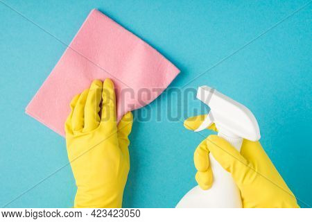 Top View Photo Of Hands In Yellow Rubber Gloves Holding Pink Viscose Rag And White Spray Bottle On I