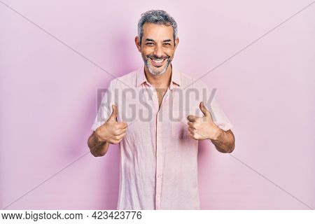 Handsome middle age man with grey hair wearing casual shirt success sign doing positive gesture with hand, thumbs up smiling and happy. cheerful expression and winner gesture.