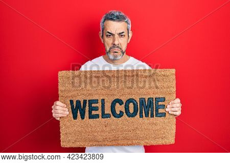 Handsome middle age man with grey hair holding welcome doormat depressed and worry for distress, crying angry and afraid. sad expression.