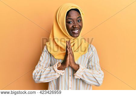 Beautiful african young woman wearing traditional islamic hijab scarf praying with hands together asking for forgiveness smiling confident.