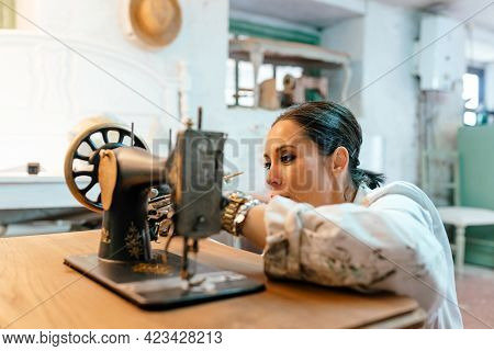 Latin Woman Painting And Restoring Old Sewing Machine In Her Workshop. Restoration, Crafts And Carpe