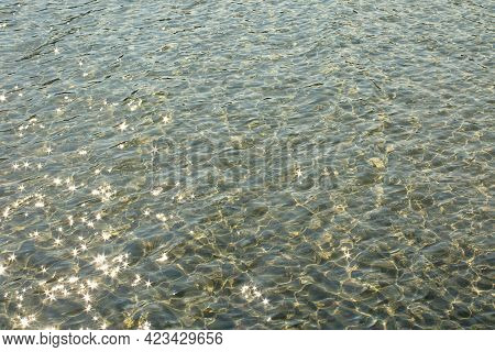 Abstract Background Of The Sea Waves With Sunbeams On The Surface.