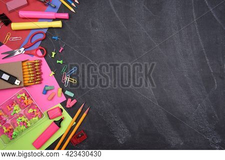 School Supplies: Still life on erased Chalkboard of assorted school supplies with copy space.
