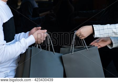 Black Shopping Bags In Male And Female Hands. Purchases In The Hands. Mockup. Black Friday Concept.