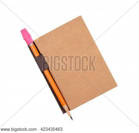 Closed pad with pencil in holder isolated on white. The plain brown pad has a blank cover with attached pencil holder tab.