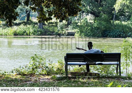 Man Playing Guitar On Bench In Audubon Park