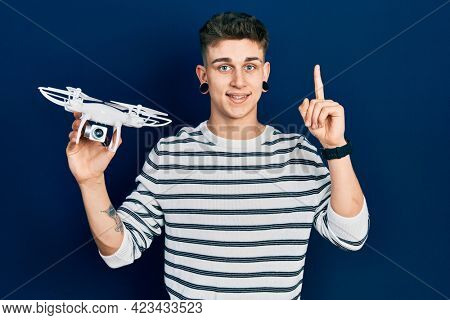 Young caucasian boy with ears dilation holding drone smiling with an idea or question pointing finger with happy face, number one