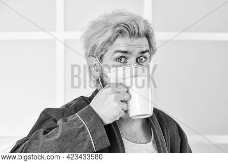 Guy In Mask Drink Tea Or Coffee At Home. Quarantine Concept. Protect Against Coronavirus. Man Wear F