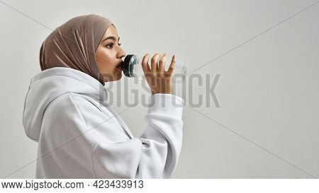 Portrait Of Young Arabic Woman In Hijab Drinking Water From Sport Bottle While Posing Sideways On Li