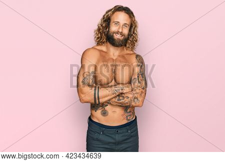 Handsome man with beard and long hair standing shirtless showing tattoos happy face smiling with crossed arms looking at the camera. positive person.