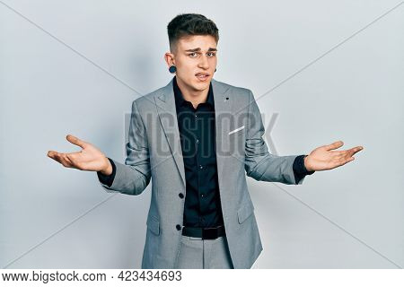 Young caucasian boy with ears dilation wearing business jacket clueless and confused with open arms, no idea concept.