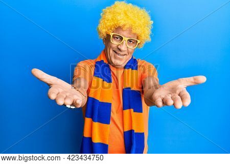 Senior hispanic man football hooligan cheering game looking at the camera smiling with open arms for hug. cheerful expression embracing happiness.