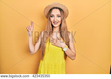 Young blonde girl wearing summer hat smiling swearing with hand on chest and fingers up, making a loyalty promise oath