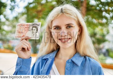 Young blonde woman holding english banknotes pounds, showing money smiling happy and confident outdoors