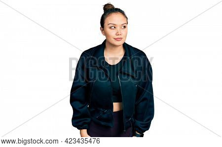 Young hispanic girl wearing sportswear smiling looking to the side and staring away thinking.