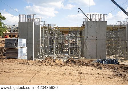 Modern Building Under Construction. Workers Set Up Scaffolding And Formwork For Pouring Concrete.