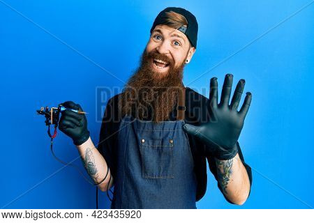Redhead man with long beard tattoo artist wearing professional uniform and gloves waiving saying hello happy and smiling, friendly welcome gesture