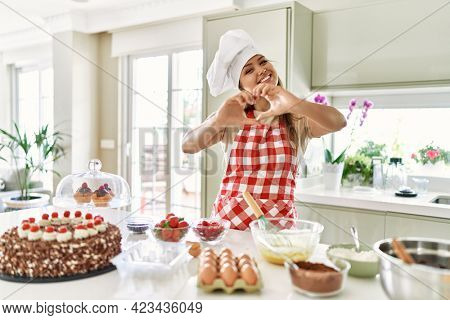 Beautiful young brunette pastry chef woman cooking pastries at the kitchen smiling in love doing heart symbol shape with hands. romantic concept.