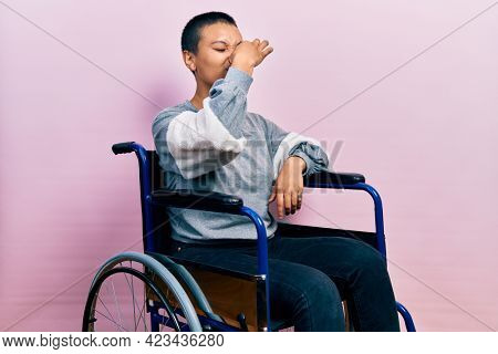 Beautiful hispanic woman with short hair sitting on wheelchair smelling something stinky and disgusting, intolerable smell, holding breath with fingers on nose. bad smell