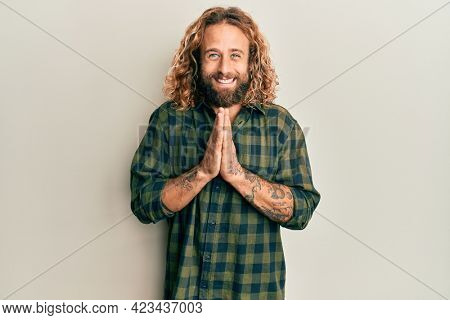 Handsome man with beard and long hair wearing casual clothes praying with hands together asking for forgiveness smiling confident.