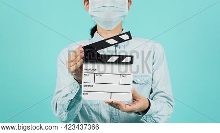 Asian Woman Wear Face Mask Or Medical Mask And Hand\'s Hold Clapper Board Or Movie Slate Use On Gree
