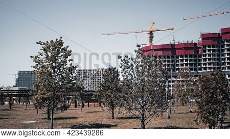 Industrial Construction Cranes Over The Houses With Red Roofs Against A Blue Sky And Trees In The Fo